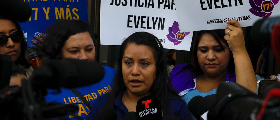 "Evelyn Hernandez, who was sentenced to 30 years in prison for a suspected abortion, speaks to the media as she arrives for a hearing in Ciudad Delgado, El Salvador July 15, 2019. Placards read ""Justice for Evelyn"". REUTERS/Jose"