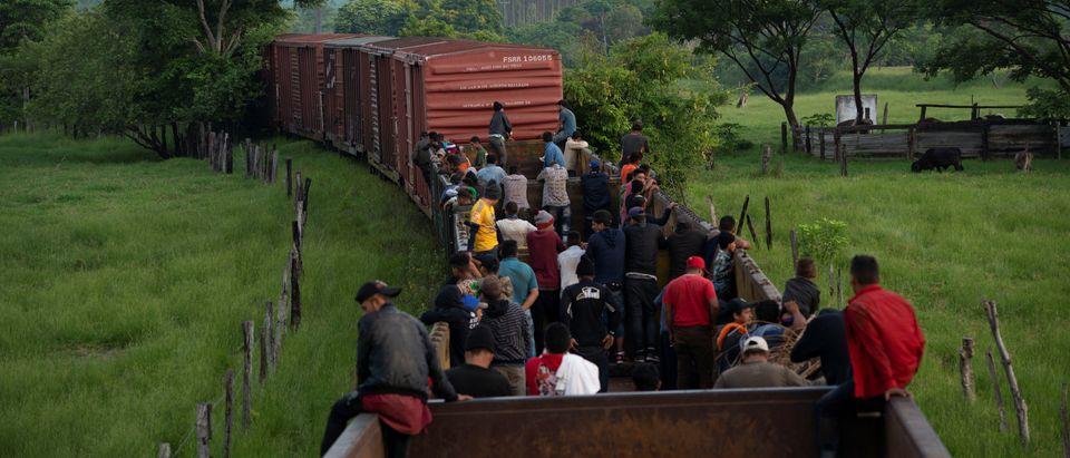 """Migrants ride on a freight train known as """"The Beast"""" as they continue their journey towards the United States, near Teapa"""