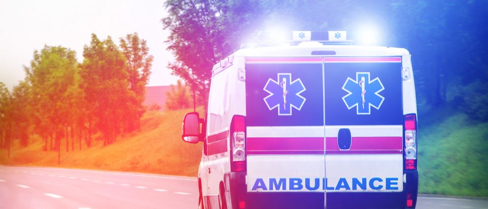 An ambulance drives down a road. Shutterstock image via OgnjenO