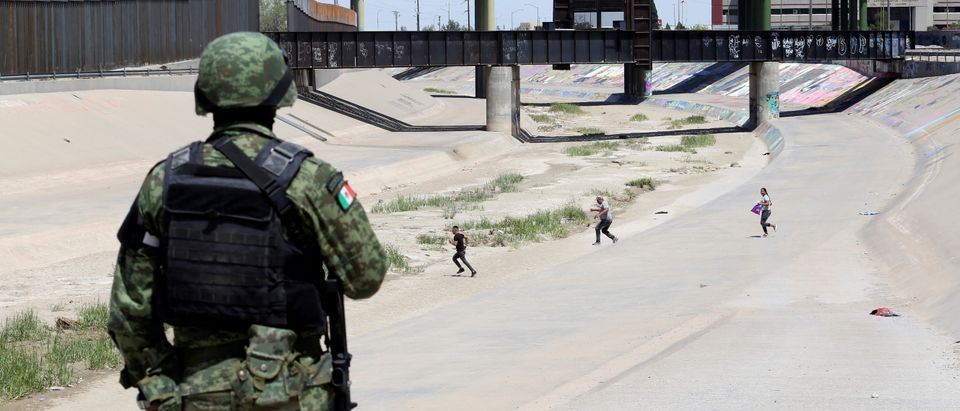 A member of the Mexican National Guard observes migrants running to cross illegally into El Paso, Texas, United States, as seen from Ciudad Juarez, Mexico June 25, 2019. REUTERS/Carlos Sanchez