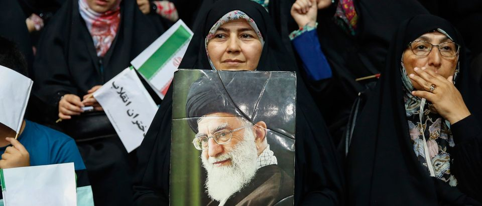 An Iranian woman holds a poster of Supreme Leader Ayatollah Ali Khamenei during a rally in support of wearing headscarves at the Sahhid Shiroudi Stadium in Tehran, on July 11, 2019. - Under Islamic law in practice in Iran since the 1979 revolution, hijab (which requires females to cover their hair and much of their body in loose clothing to prevent their figures being seen) is obligatory for local and foreign women in the country. (Photo by - / AFP) (Photo credit should read -/AFP/Getty Images)