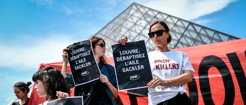 "Activists of P.A.I.N. (Prescription Addiction Intervention Now) association - created to respond to the opioid crisis - and of French NGO Aides hold banners reading ""Shame on Sackler"" and ""Take down the Sackler name"" (back) in front of the Pyramid of the Louvre museum (Pyramide du Louvre), on July 1, 2019 in Paris, during a protest to condemn the museum's ties with the Sackler family, billionaire donors accused of pushing to sell a highly addictive painkiller blamed for tens of thousands of deaths. (STEPHANE DE SAKUTIN/AFP/Getty Images)"