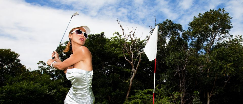 A woman plays golf in a minidress. Shutterstock image via plprod