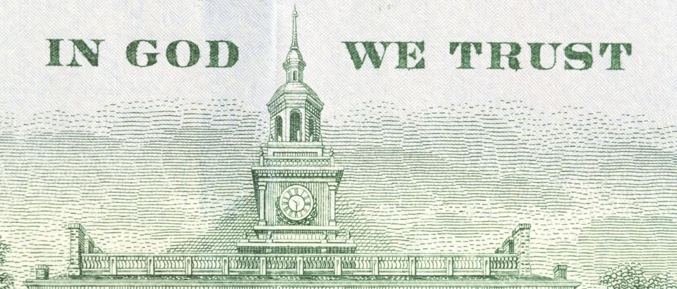 Close view of In God We Trust and Independence Hall on the back of an American hundred dollar bill. (BW Folsom/Shutterstock)