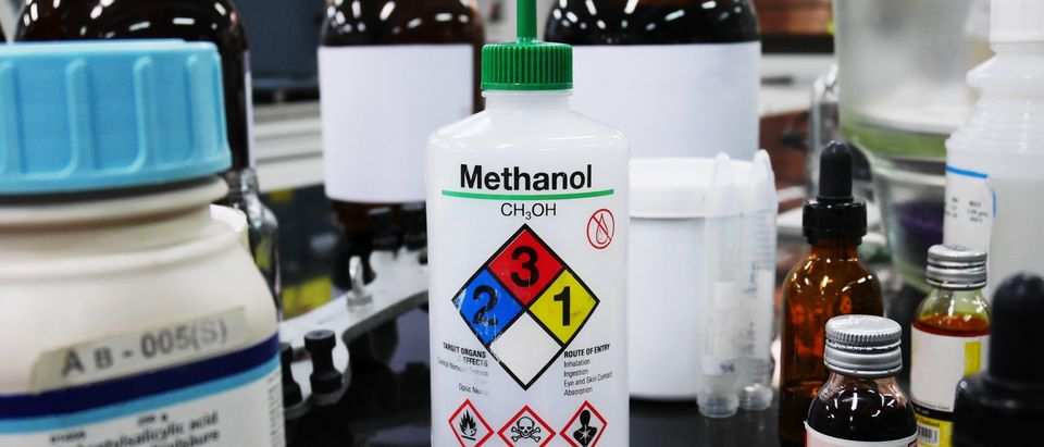 Bottle of Methanol and chemical with hazard warning symbols for experiment in Laboratory with Variety type of chemical container background. (Shutterstock)