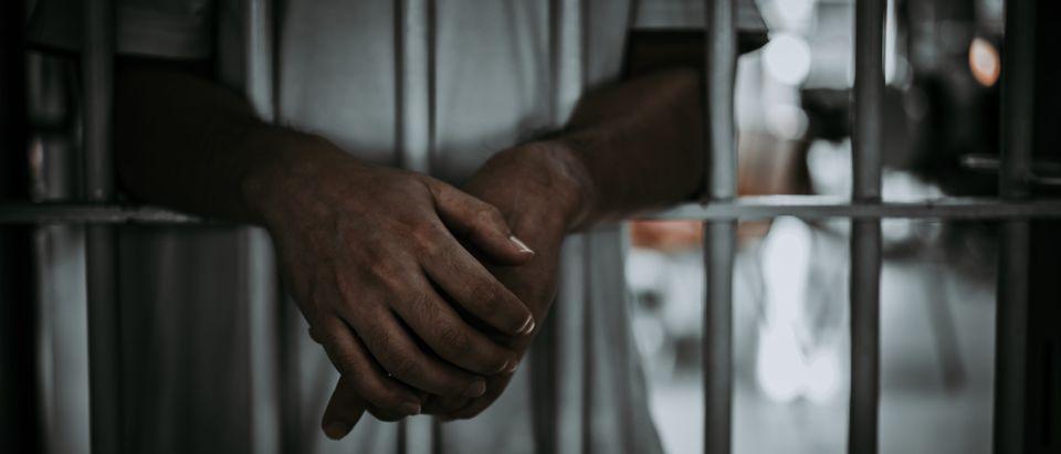 A man is in prison. Shutterstock image via kittirat roekburi
