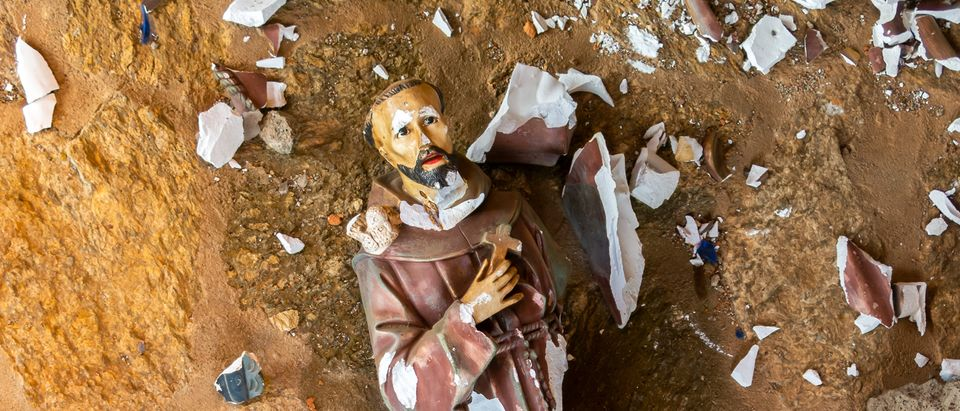 A statue of a priest lies broken on the ground. Shutterstock image via Tacio Philip Sansonovski