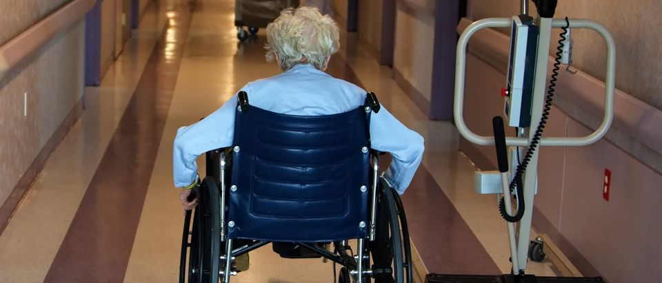 An elderly woman in a wheel chair traveling down a nursing home corridor. (fadedphotoshop/Shutterstock)