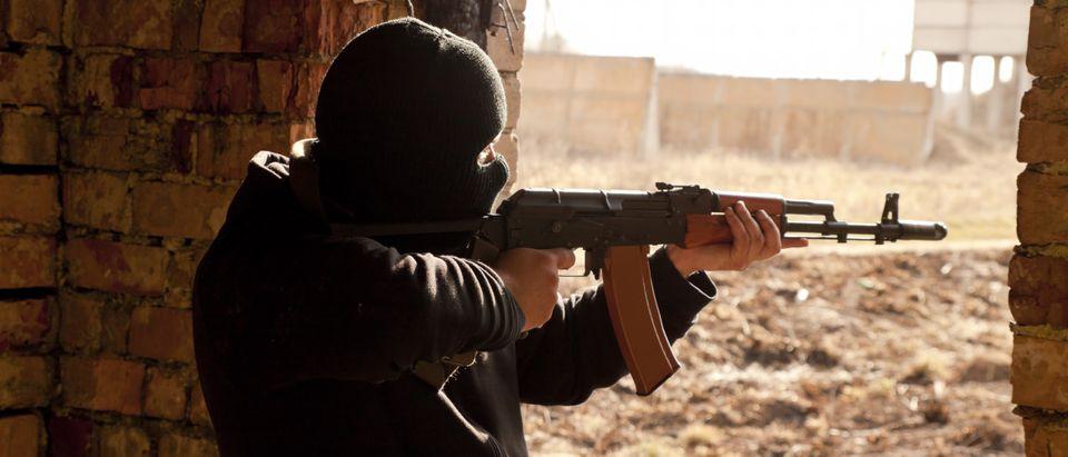 A man holds a gun. Shutterstock image via user grassy22