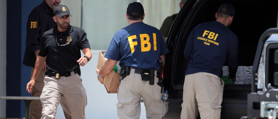 FBI personnel load boxes into a car as they search the anti-narcotics police division during a raid, in Vega Baja