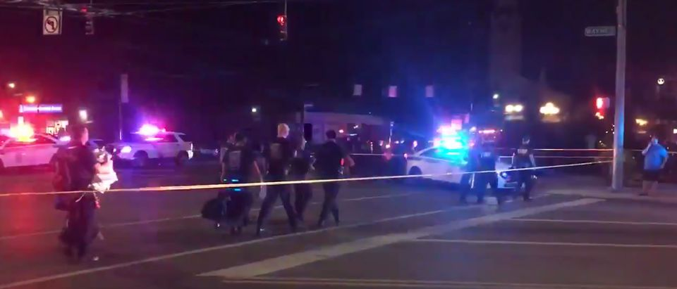 This videograb taken from the Twitter account of Derek Myers on August 4, 2019 shows police officers walking behind police cordon following a mass shooting in the popular bar and nightlife Oregon district in Dayton, Ohio (DEREK MYERS/AFP/Getty Images)