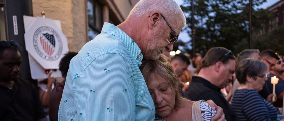 People comfort each other as they take part of a candle lit vigil in honor of those who lost their lives or were wounded in a shooting in Dayton, Ohio, on Aug. 4, 2019. (MEGAN JELINGER/AFP/Getty Images)