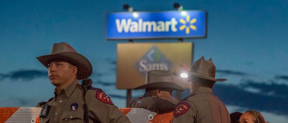 "Texas State Troopers keep watch at the makeshift memorial for victims of the shooting that left a total of 22 people dead at the Cielo Vista Mall WalMart in El Paso, Texas, on August 6, 2019. - US President Donald Trump on Monday urged Republicans and Democrats to agree on tighter gun control and suggested legislation could be linked to immigration reform after two shootings left 30 people dead and sparked accusations that his rhetoric was part of the problem. ""Republicans and Democrats must come together and get strong background checks, perhaps marrying this legislation with desperately needed immigration reform,"" Trump tweeted as he prepared to address the nation on two weekend shootings in Texas and Ohio. ""We must have something good, if not GREAT, come out of these two tragic events!"" Trump wrote. (Photo by Mark RALSTON/AFP/Getty Images)"