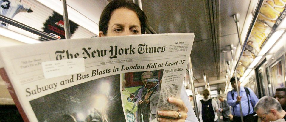Risa Turken reads The New York Times with an article about the London terror attacks while riding the subway during the morning rush hour July 8, 2005 in New York City. (Photo by Mario Tama/Getty Images)