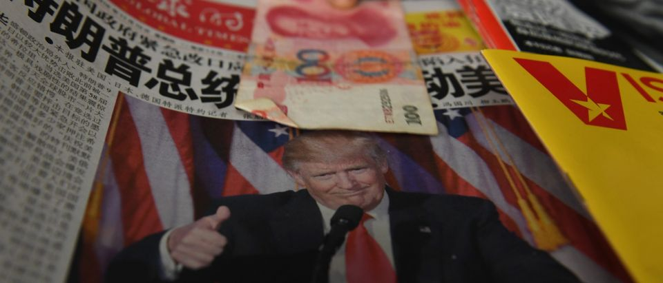 A vendor picks up a 100 yuan note above a newspaper featuring a photo of US president-elect Donald Trump, at a news stand in Beijing on November 10, 2016. The world's second-largest economy is US president-elect Donald Trump's designated bogeyman, threatening it on the campaign trail with tariffs for stealing American jobs, but analysts say US protectionism could create opportunities for Beijing. / AFP / GREG BAKER (Photo credit should read GREG BAKER/AFP/Getty Images)