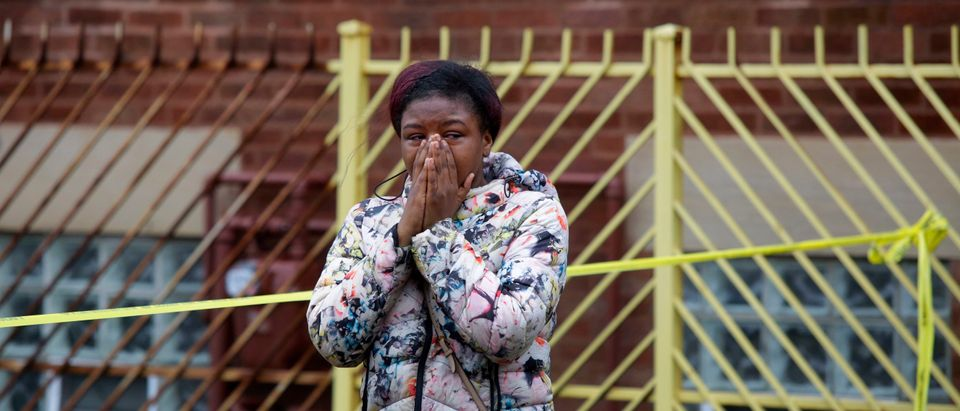 A woman grieves as she reacts to a shooting that left four people dead at a restaurant in the 2700 block of East 75th Street on March 30, 2017 in Chicago, Illinois. (Photo by Joshua Lott/Getty Images)