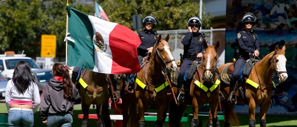Students carrying Mexico's flag walk past mounted San Diego Police officers during protest at Chicano Park near downtown San Diego