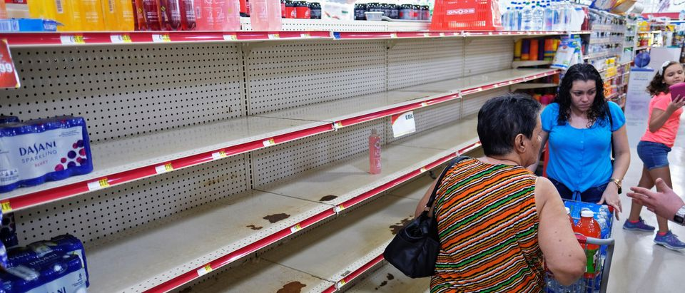 Nearly empty shelves where bottled water is normally displayed, are shown at a grocery store as Tropical Storm Dorian approaches in Cabo Rojo, Puerto Rico, Aug. 26, 2019. (REUTERS/Ricardo Arduengo)
