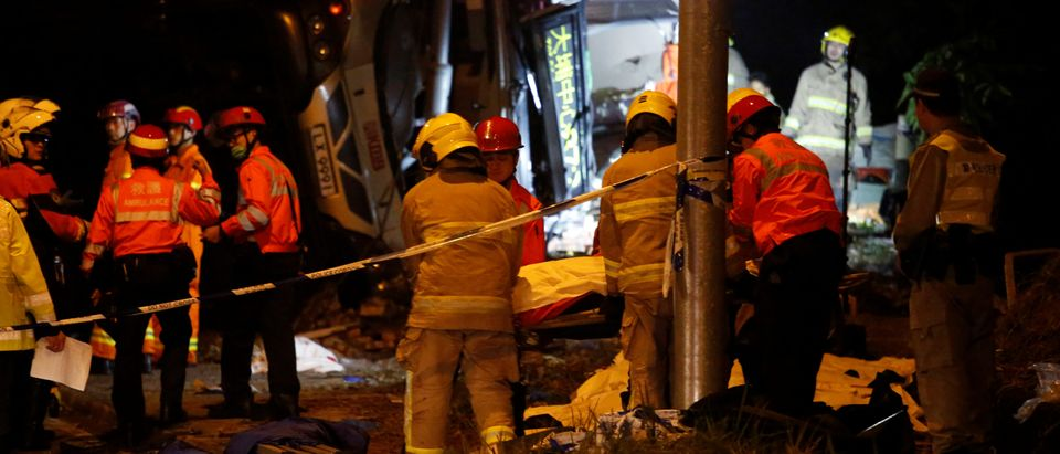 Rescuers carry a body in front of a crashed bus in Hong Kong, China February 10, 2018. REUTERS/Bobby Yip