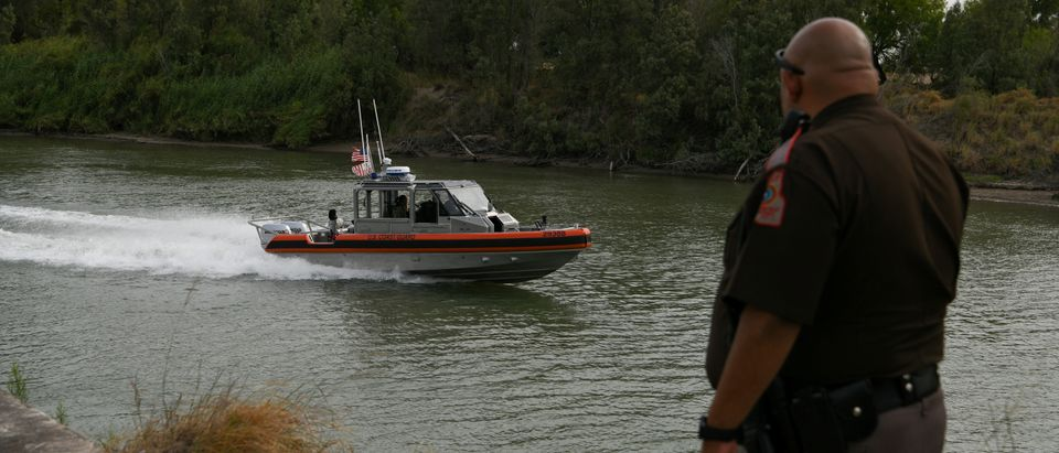 A U.S. Coast Guard boat deployed for U.S.-Mexico border security operations navigates the Rio Grande as a constable department deputy looks on near Penitas