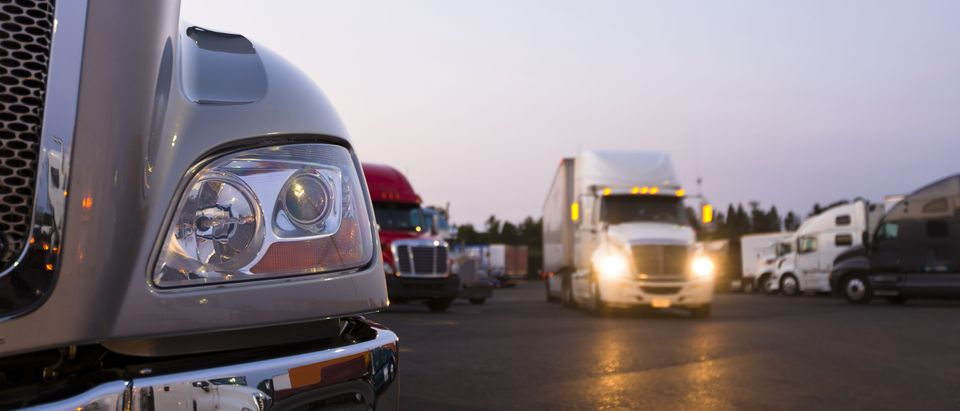 Fragment of the modern parts of the truck on a night truck stop in the foreground to the background of semi trucks at the parking places and a moving semi truck with its headlights on. Shutterstock
