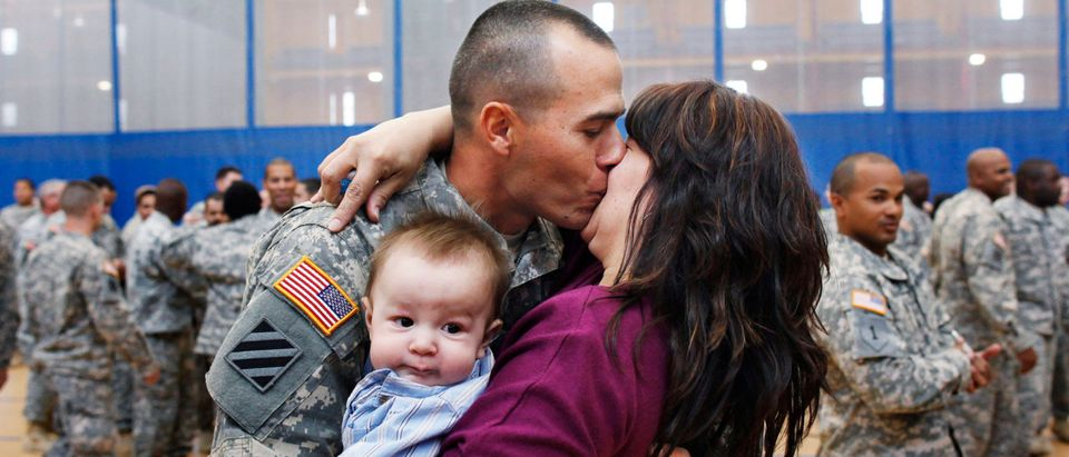 Staff Sgt. Keith Fidler kisses his wife Cynthia, as their son Kolin looks on, during a homecoming ceremony in New York, April 8, 2011 for the New York Army National Guard's 442nd Military Police Company's return from Iraq. REUTERS/Shannon Stapleton