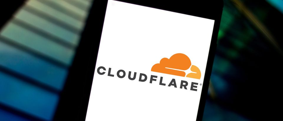 The Cloudflare logo is displayed on a smartphone screen. Shutterstock image via rafapress