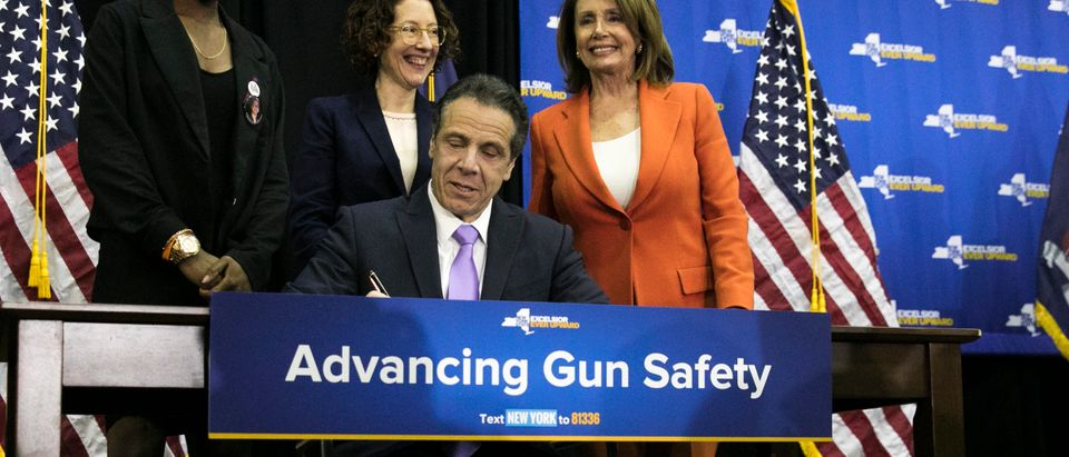 NEW YORK, NY - MAY 1: Surrounded by (L to R) Aalayah Eastmond, who survived the shooting at Marjory Stoneman Douglas High School in Parkland, Florida, Amy Barasc, executive director of Her Justice organization, and House Minority Leader Nancy Pelosi (D-CA), New York Governor Andrew Cuomo signs a gun safety bill at John Jay College, May 1, 2018 in New York City. Governor Cuomo signed a bill ensuring domestic abusers are prohibited from possessing handguns and long guns in New York State. The bill also prohibits anyone with an outstanding warrant, felony, or other serious offenses from receiving or renewing a firearm license. (Photo by Drew Angerer/Getty Images)
