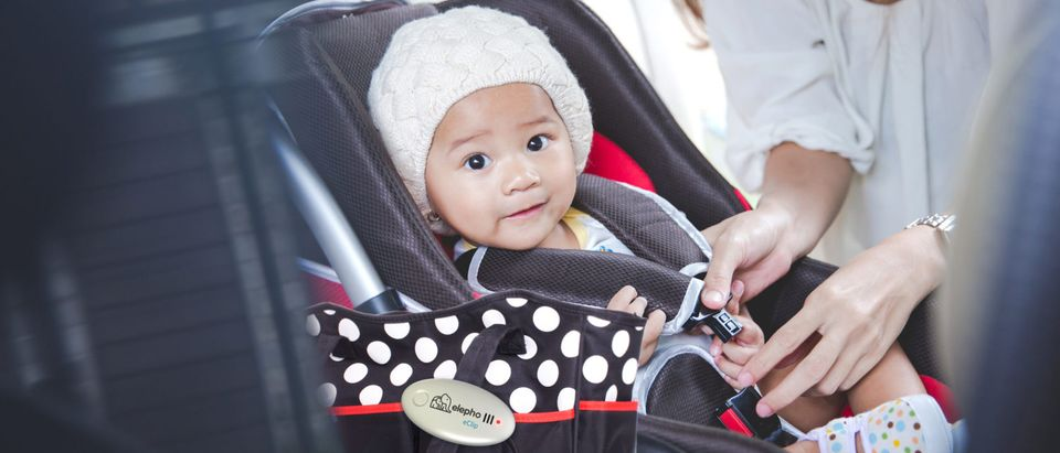 A mother straps her baby into a car seat while using the eClip Baby Reminder. (Elepho)