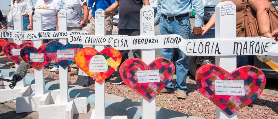 People pray beside crosses with the names of victims who died in the shooting to a makeshift memorial after the shooting that left 22 people dead at the Cielo Vista Mall WalMart in El Paso, Texas, on August 5, 2019 (MARK RALSTON/AFP/Getty Images)