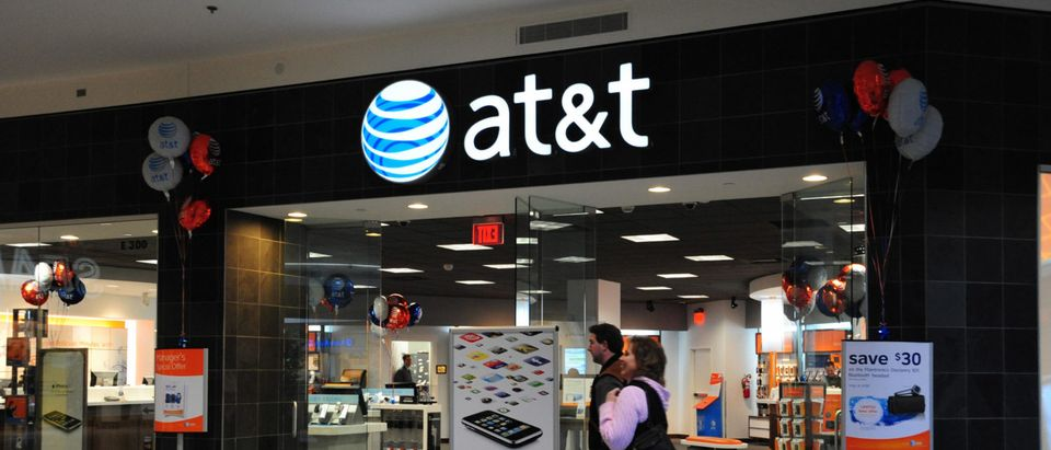 Shoppers pass an AT&T phone store on Feb