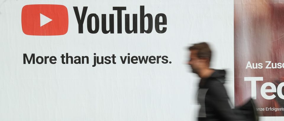 A man walks past a billboard advertisement for YouTube on October 5, 2018 in Berlin, Germany. YouTube has established itself as the biggest global platform for online video presentations. (Photo by Sean Gallup/Getty Images)