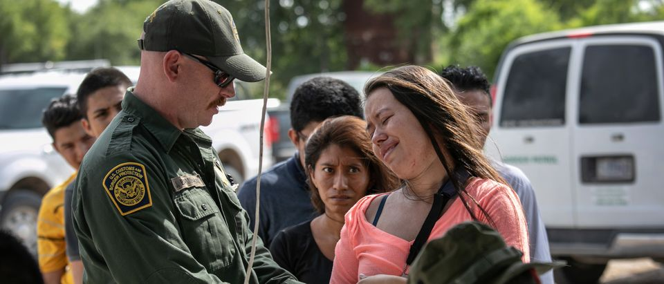 LOS EBANOS, TEXAS - JULY 02: A U.S. Border Patrol checks the arm of an immigrant from Guatemala after taking her into custody on July 02, 2019 in Los Ebanos, Texas. The woman said she was in pain from a recent surgery on her shoulder. Hundreds of immigrants, most from Central America, turned themselves in to border agents after rafting across the Rio Grande from Mexico to seek political asylum in the United States. They were then to be sent to a Border Patrol processing center in McAllen, Tx. (Photo by John Moore/Getty Images)