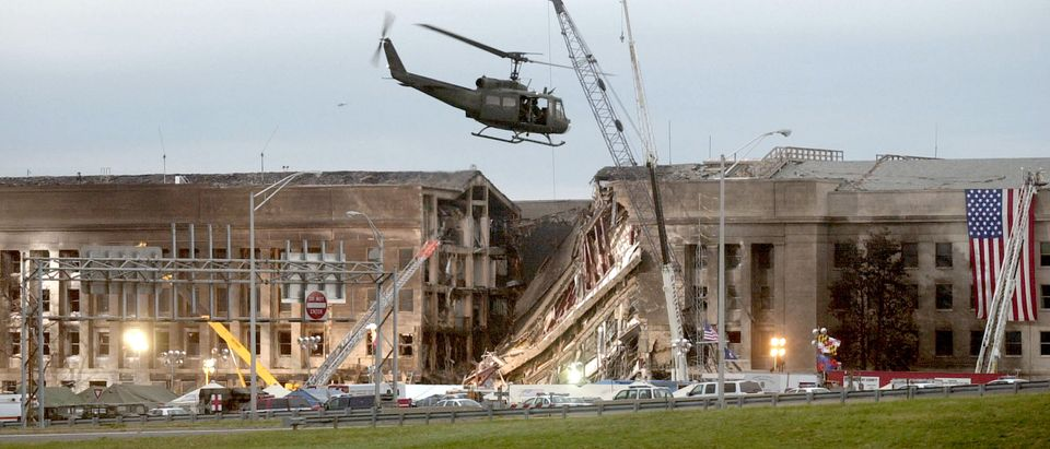 A military helicopter flies in front of the Pentagon September 14, 2001 in Arlington, Virginia at the impact site where a hijacked airliner crashed into the building. (Photo by Stephen J. Boitano/Getty Images)
