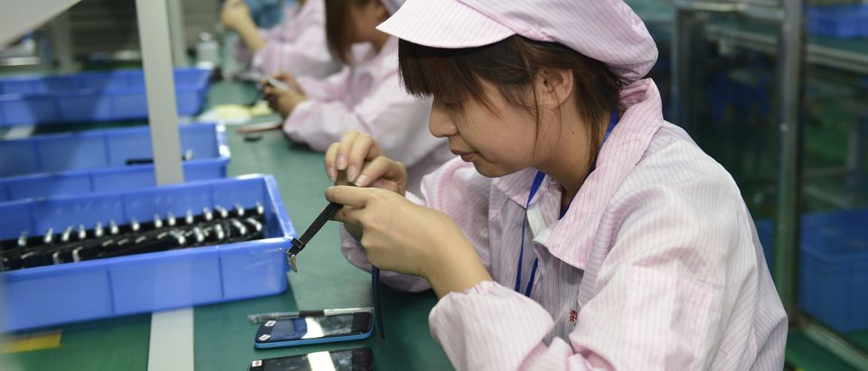 This picture taken on April 22, 2015 shows Chinese workers assembling a cheaper local alternative to the Apple Watch in a factory producing thousands every day in Shenzhen, in southern China's Guangdong province. (Photo: STR/AFP/Getty Images)