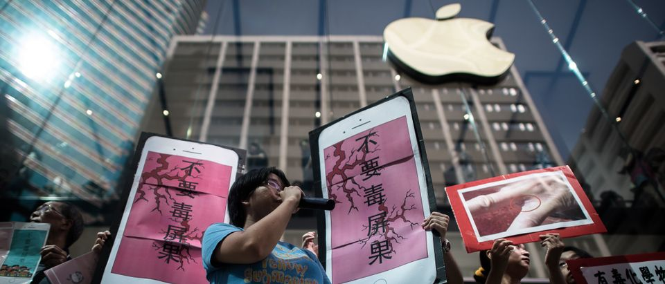 Rights campaigners stage a protest coinciding with the launch of the new iPhone 6s outside an Apple store in Hong Kong on September 25, 2015. Apple was urged to act as rights campaigners said a Chinese touchscreen glass supplier to the smartphone giant was exploiting factory workers. AFP PHOTO / Philippe Lopez /Getty Images