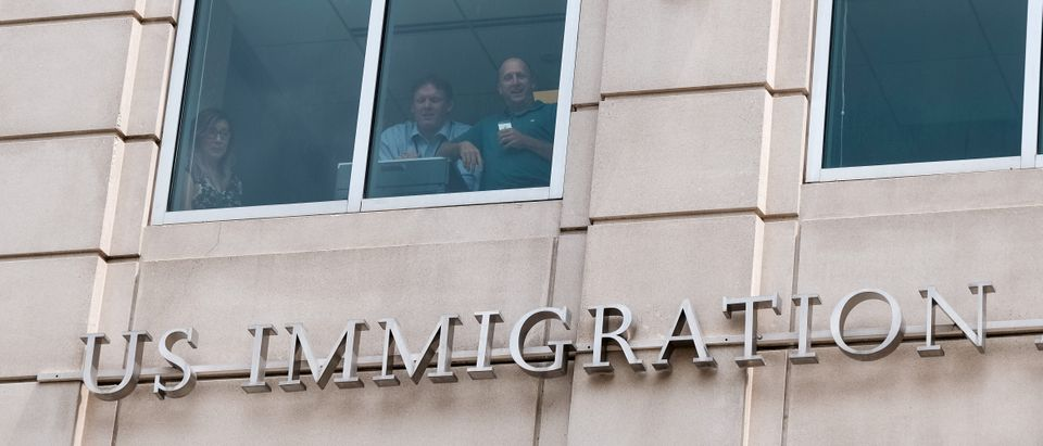 """U.S. Immigration and Customs Enforcement employees watch from a window as activists hold the """"Shutdown ICE"""" rally in Washington"""