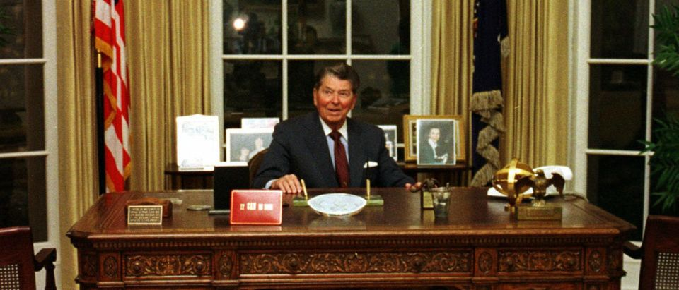 Former United States president Ronald Reagan poses in the replica of the Oval Office at the Ronald R..