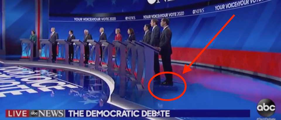 Julian Castro stands on booster box on debate stage. Screen Shot/ABC News