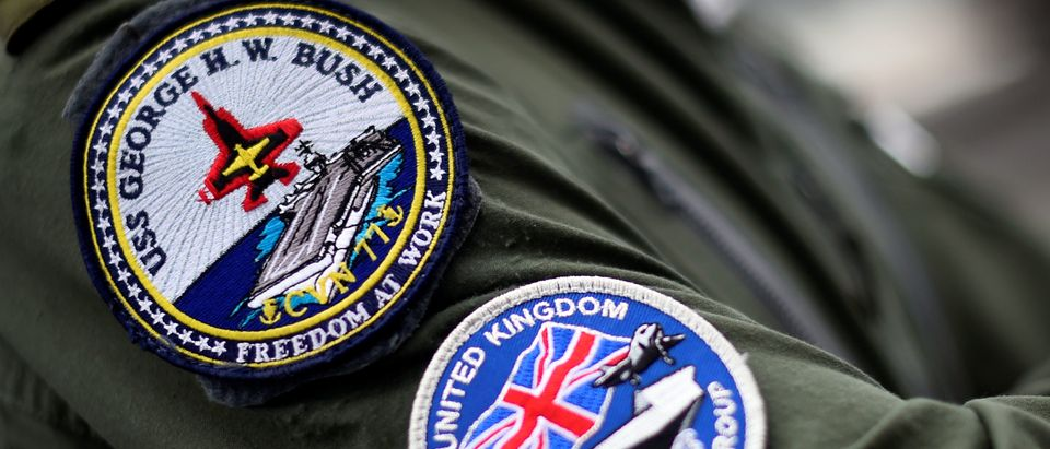 Badges on the sleeve of a Royal Navy officer are seen onboard the USS George H.W. Bush aircraft carrier anchored off Stokes Bay in the Solent