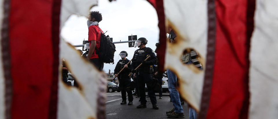 Police in riot gear and a protester stand near a burned U.S. flag after the not guilty verdict in the murder trial of Jason Stockley, a former St. Louis police officer charged with the 2011 shooting of Anthony Lamar Smith, in St. Louis, Missouri, U.S. September 17, 2017. Picture taken September 17, 2017. REUTERS/Lawrence Bryant