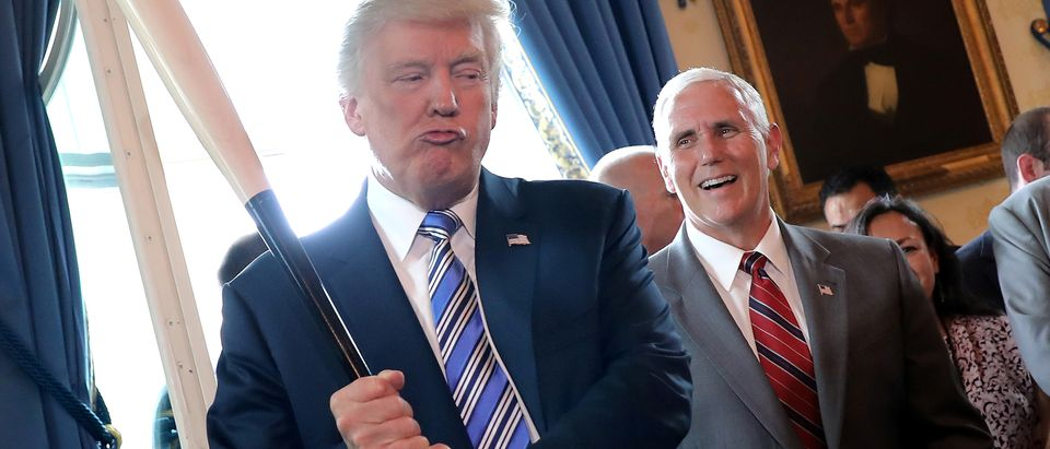 Vice President Mike Pence laughs as U.S. President Donald Trump holds a baseball bat. REUTERS/Carlos Barria