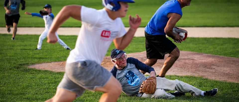 """2020 Democratic U.S. presidential candidate and U.S. Senator Bernie Sanders dives for the ball during a baseball game between his staff, """"The Revolutionaries,"""" and the Leaders Believers Achievers Foundation at the """"Field of Dreams"""" movie site in Dyersville"""