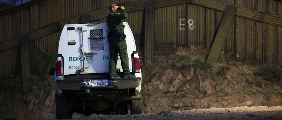 A U.S. Customs and Border Protection agent surveys the border fence in Nogales, Arizona. Shutterstock
