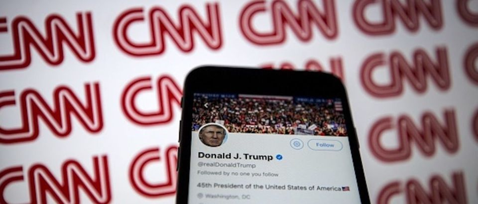 Donald Trump's Twitter profile is seen on a smartphone against a backdrop with the CNN logo, in Ankara, Turkey on December 9, 2018
