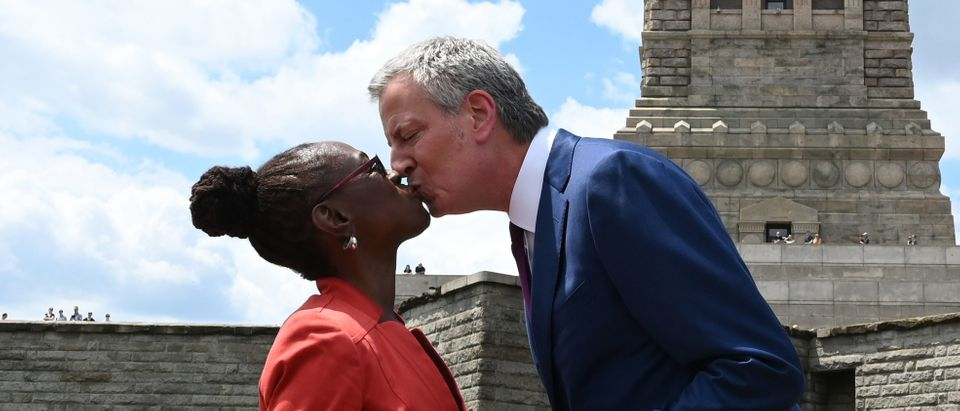 New York City Mayor Bill de Blasio and his wife, Chirlane McCray kiss as they arrive at Liberty Island for the Statue of Liberty Museum Dedication ceremony on May 16, 2019. (TIMOTHY A. CLARY/AFP/Getty Images)