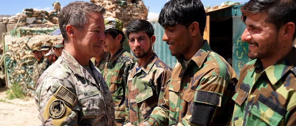 In this photo taken on June 6, 2019, commander of U.S. and NATO forces in Afghanistan General Scott Miller (L) shakes hands with Afghan National Army (ANA) soldiers during a visit at a checkpoint in Nerkh district of Wardak province in west Kabul. (Photo: THOMAS WATKINS/AFP/Getty Images)