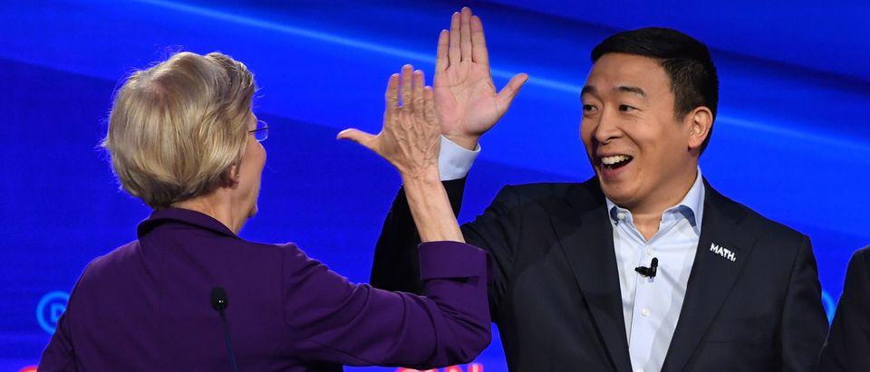 Democratic presidential hopeful Massachusetts Sen. Elizabeth Warren (L) hi-fives entrepreneur Andrew Yang (C). (Photo by SAUL LOEB/AFP via Getty Images)