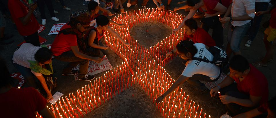 AIDS activists light a group of candles placed in the shape of a red ribbon during an event marking World AIDS Day in Manila on Dec. 1, 2012. Discrimination against homosexuals and people infected with HIV is contributing to the rapid rise of the incurable disease in the Philippines, officials and health activists said. TED ALJIBE/AFP/Getty Images