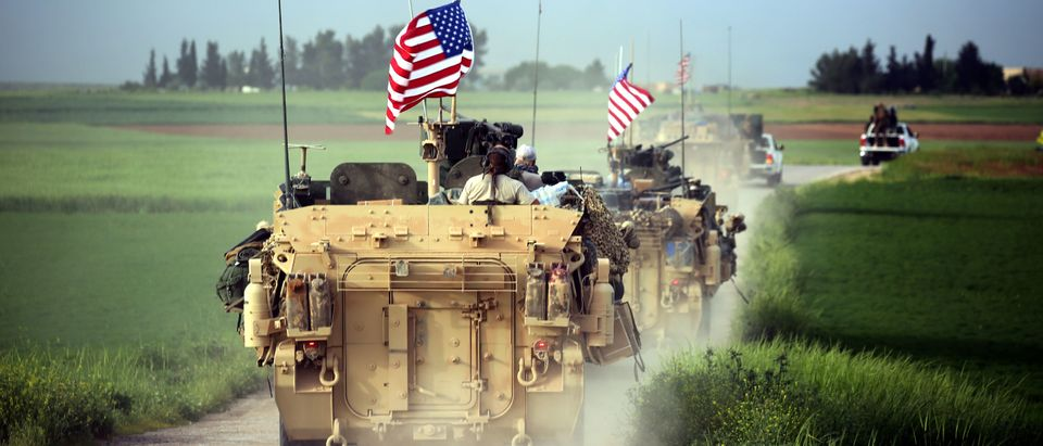 US forces, accompanied by Kurdish People's Protection Units (YPG) fighters, drive their armoured vehicles near the northern Syrian village of Darbasiyah, on the border with Turkey on April 28, 2017. (Photo credit should read DELIL SOULEIMAN/AFP/Getty Images)